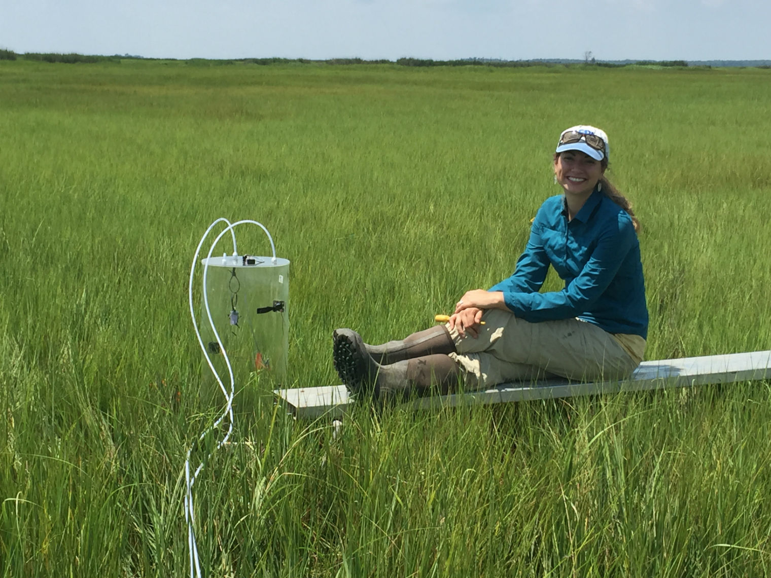 Post-doctoral researcher Rose Martin fits a greenhouse gas flux chamber to the marsh.